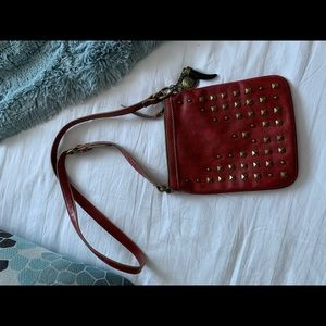 Small red crossbody with gold studs.
